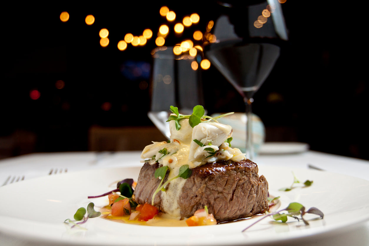 Steak topped with creamy sauce accompanied by two glasses of red wine