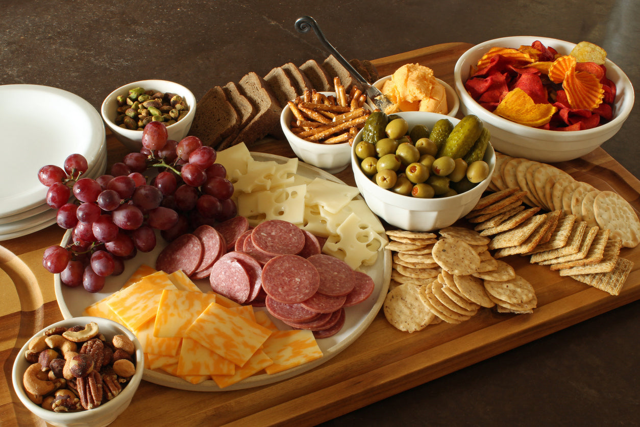 A charcuterie board full with fruits, crackers, cheese, and salami