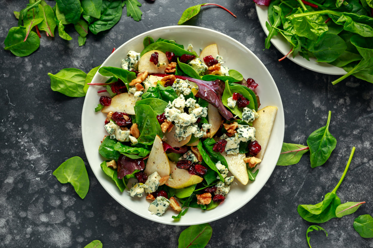 A salad with pears, walnuts, cranberries, and a fig and lemon poppyseed dressing