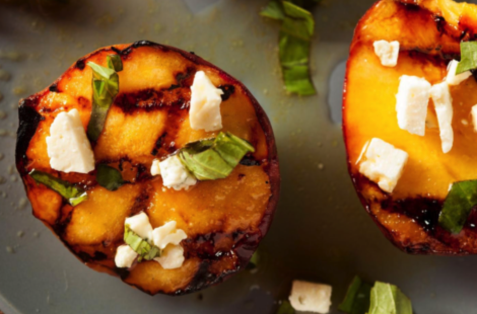 Grilled peaches topped with cheese crumbles and basil