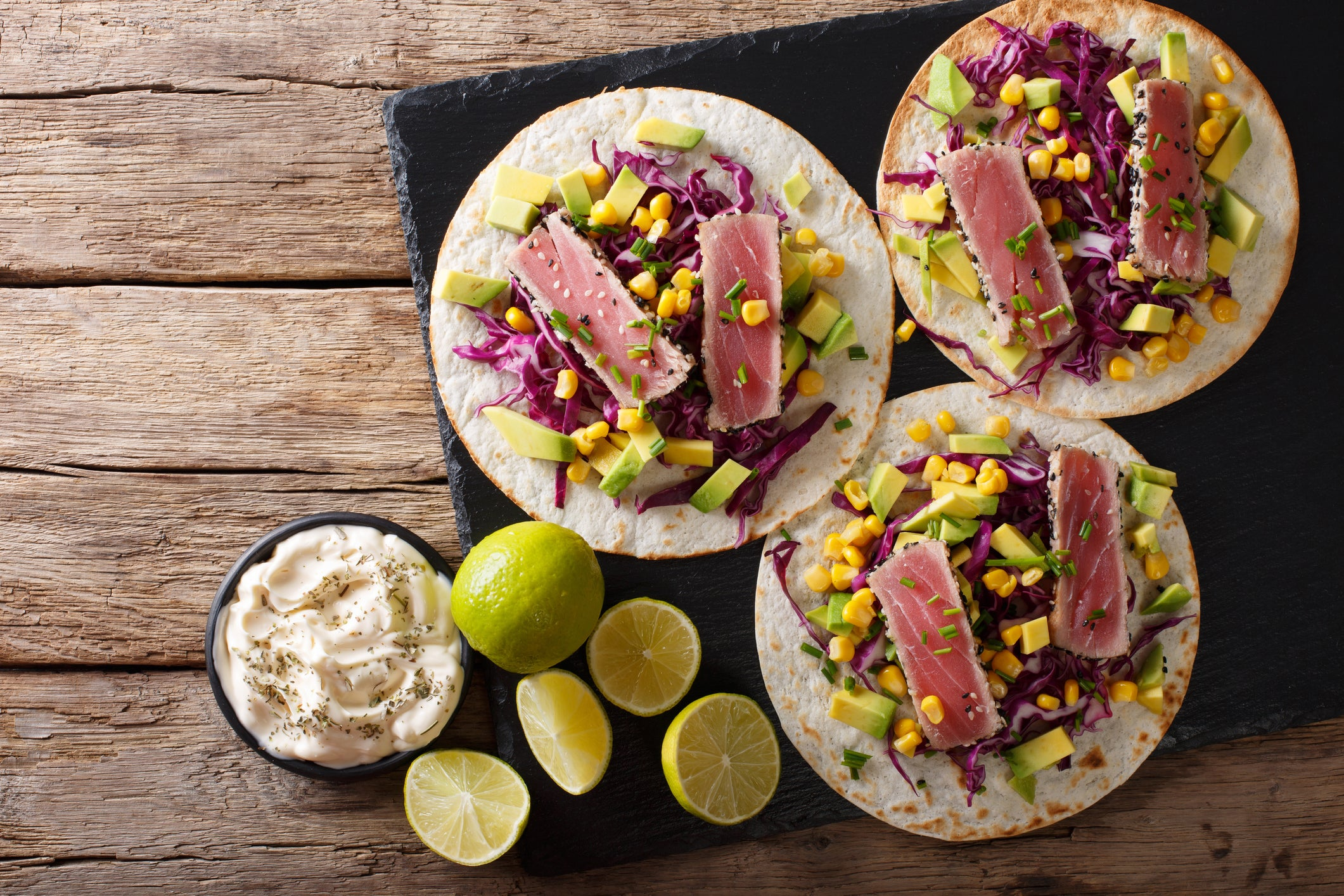 Seared tuna tacos on a platter next to lime and dip