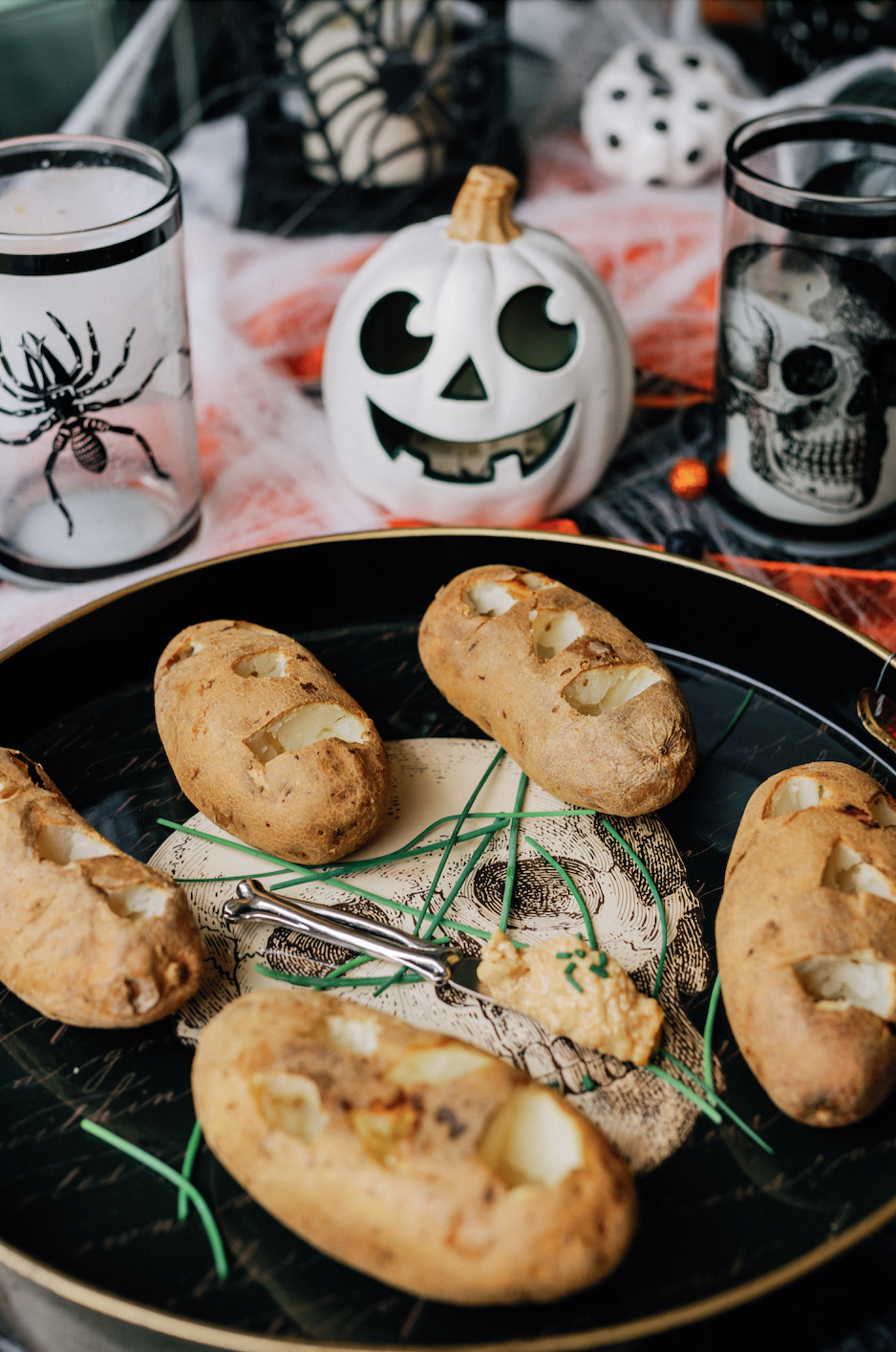 Baked potatoes on a plate have been cut to resemble shrunken potato heads. Halloween decorations surround them