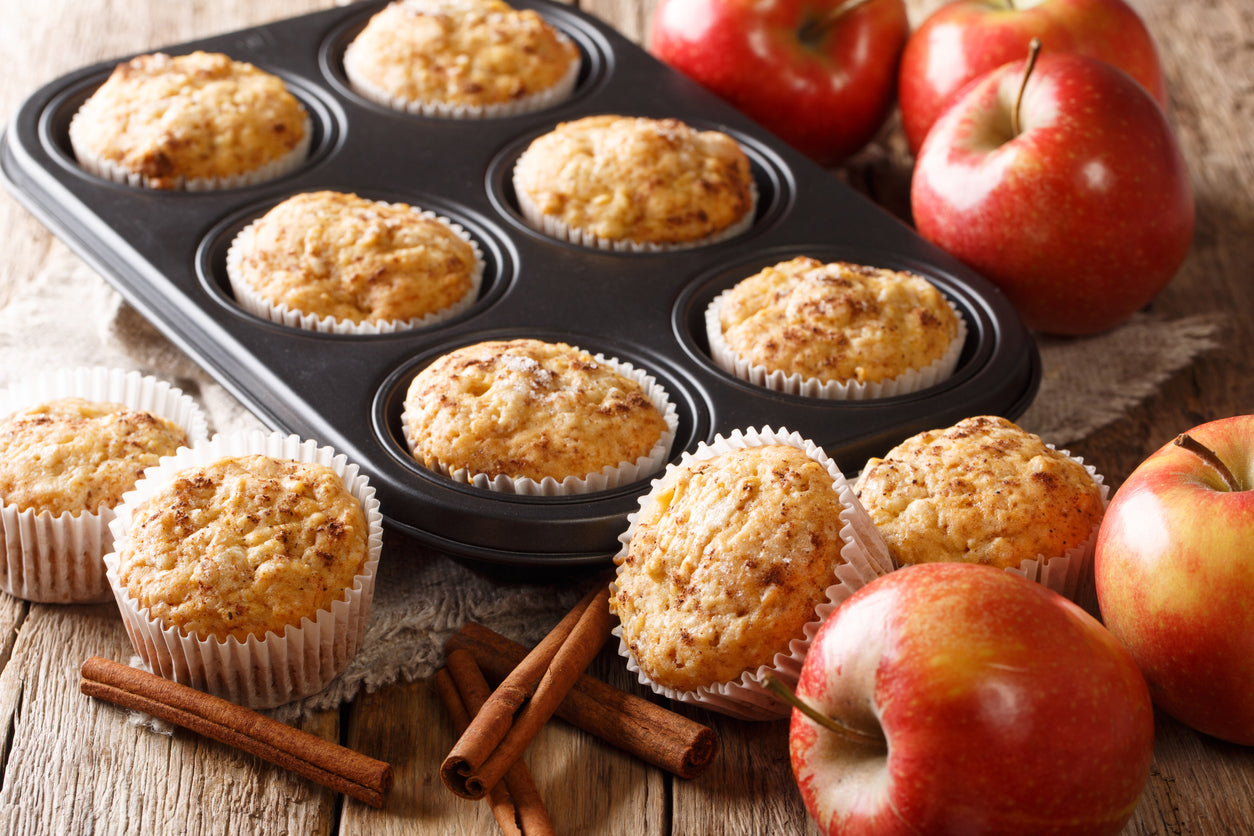 Pan of apple cinnamon muffins surrounded by apples and cinnamon sticks.