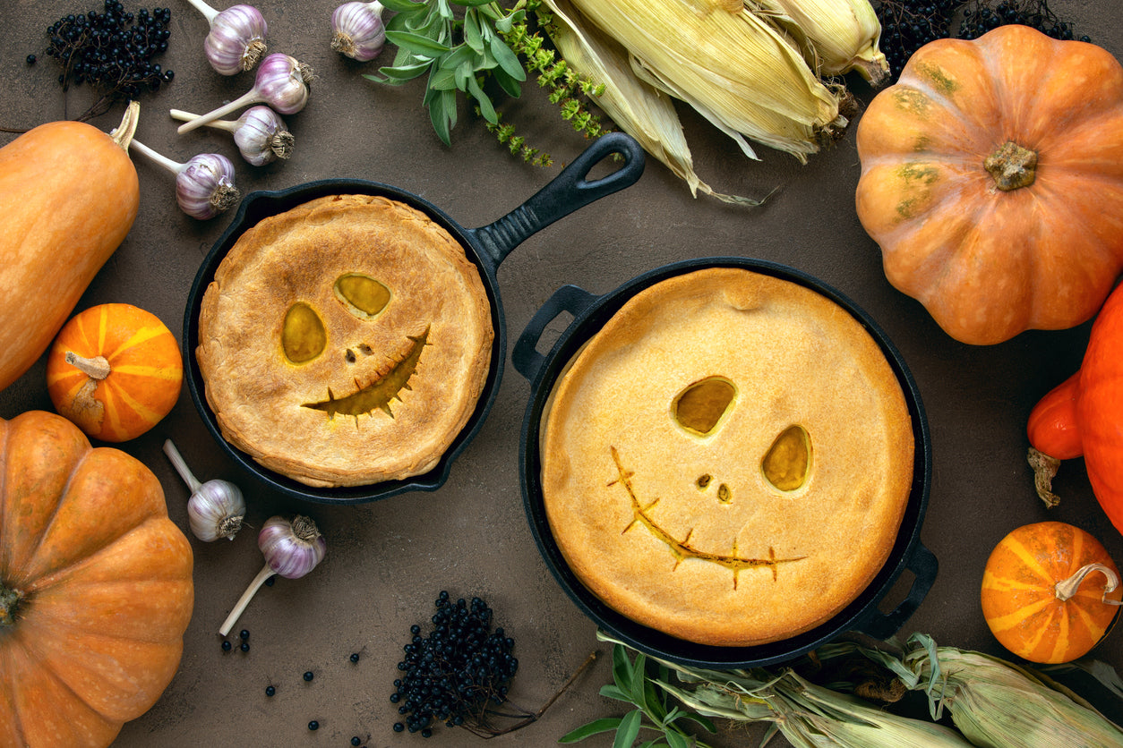Pies with jack-o-lantern faces in cast iron pans on a table with pumpkins, squash, corn, and garlic.