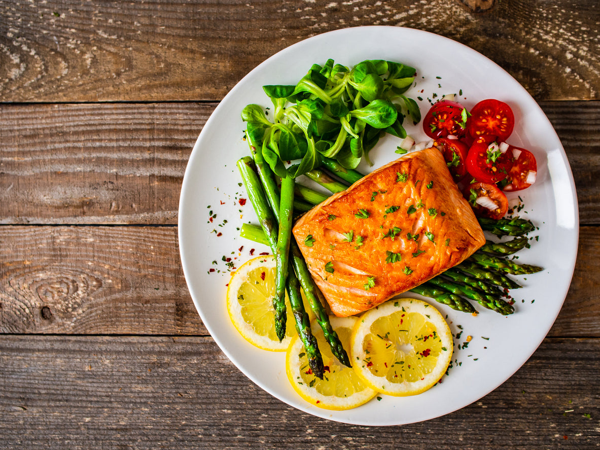 Baked salmon on a plate surrounded by asparagus, tomatoes, salad and slices of lemon.