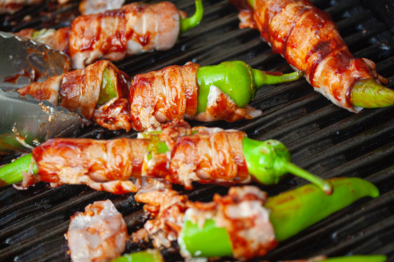 Bacon wrapped jalapeños on a grill.