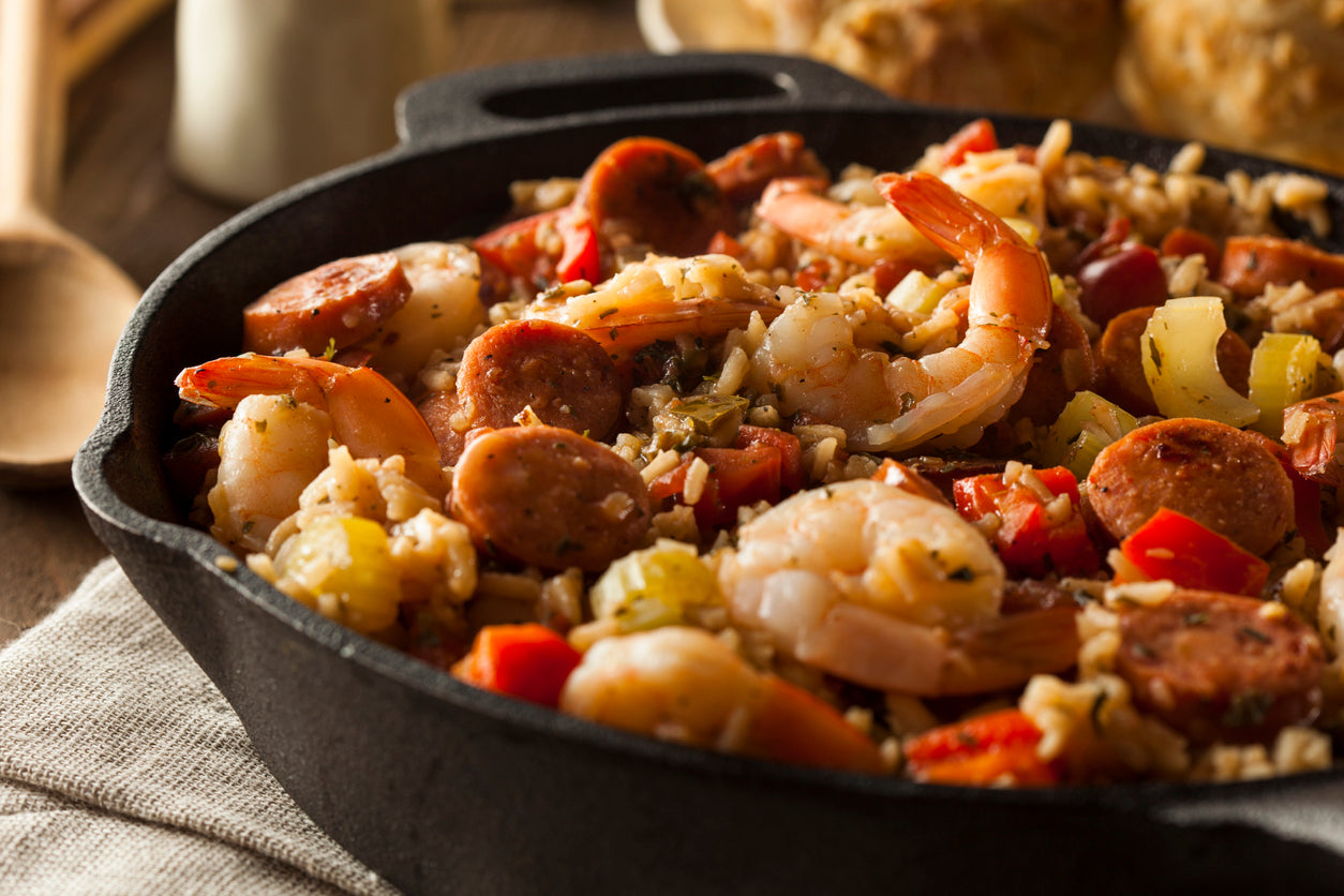 Shrimp jambalaya in a cast iron pan with vegetables and rice.