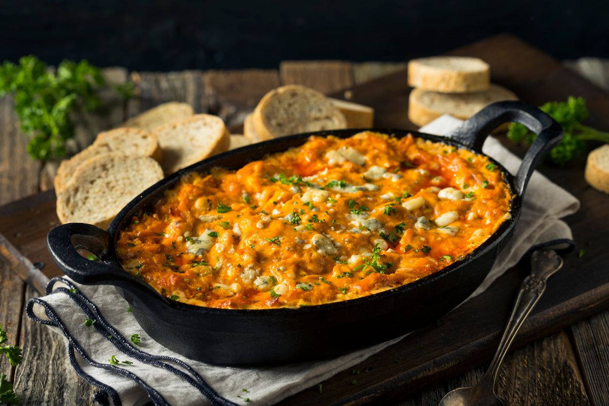 Chicken dip in a skillet. Topped with blue cheese and bread beside it for dipping