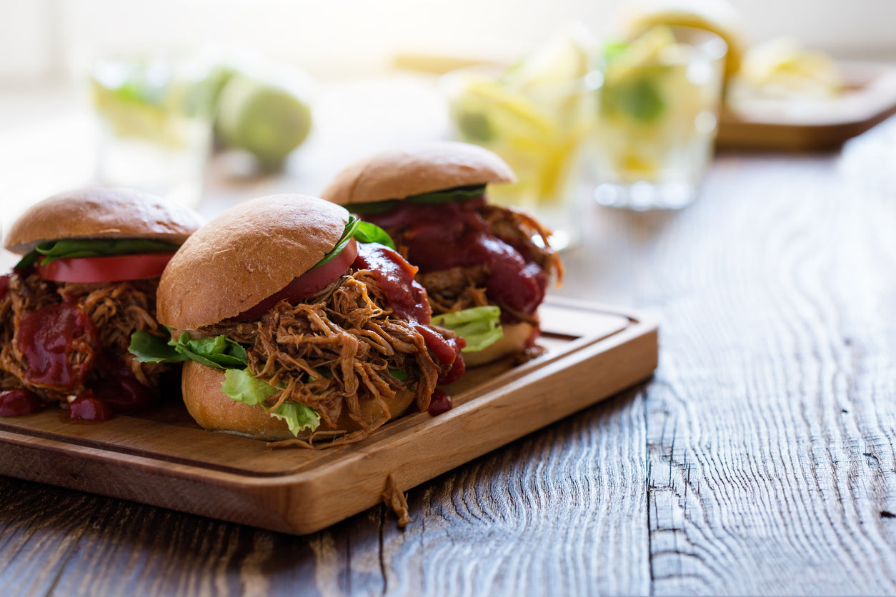 Pulled pork sliders with lettuce, tomatoes, and barbecue sauce on a cutting board.