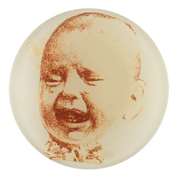 A four inch round decoupage plate titled Crying Baby (Left)
