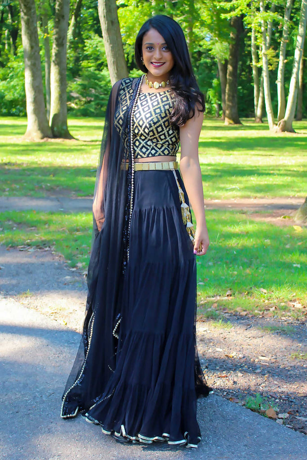 Layered and ruffled black lehnga with gold trim and a modern twist. Blouse covered in gold scalloped design with a chic patern.  2 piece lehnga can be complete with or without the black chiffon dupatta on shoulders/ shoulder.