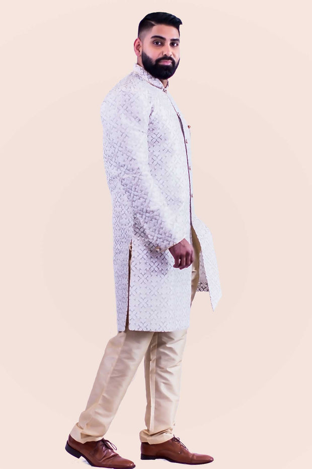 Kurta style sherwani, silk blend with a with gold buttons from collar to mid torso. This kurta is paired with a neutral color pants.