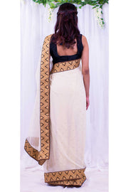 Angelic cream chiffon sari covered in gold specks, with heavy golden border designed with bindi appearing details.