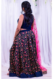 Two piece lehenga with high slit in blue skirt, covered in pink flower embroidery and gold stems. Paired with lacy blue blouse. Finish this look by draping hot pink dupatta with flower border on shoulders/ shoulder.