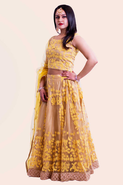 Bright yellow two piece lehenga with yellow flower embroidered overlay. Skirt has gorgeous cage copper design border. Finish this look by draping matching yellow dupatta on shoulders/ shoulder.