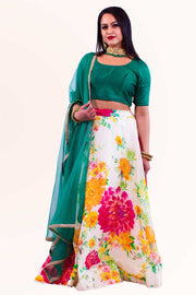 Sophiscated green blouse with midlength sleeves, paired with skirt covered in floral print. To be styled with matching green dupatta for draping.