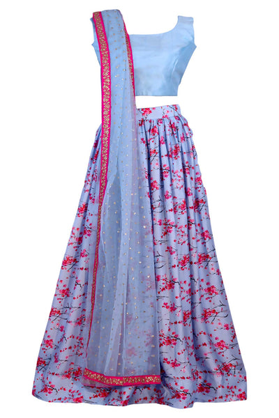 Satin lehenga with decadence, covered in cherry blossom print over a sky blue tone on skirt. Paired with matching blouse. Finish this look with a dupatta with a beautiful contrast border with light sequence for the perfect amount of sparkle.