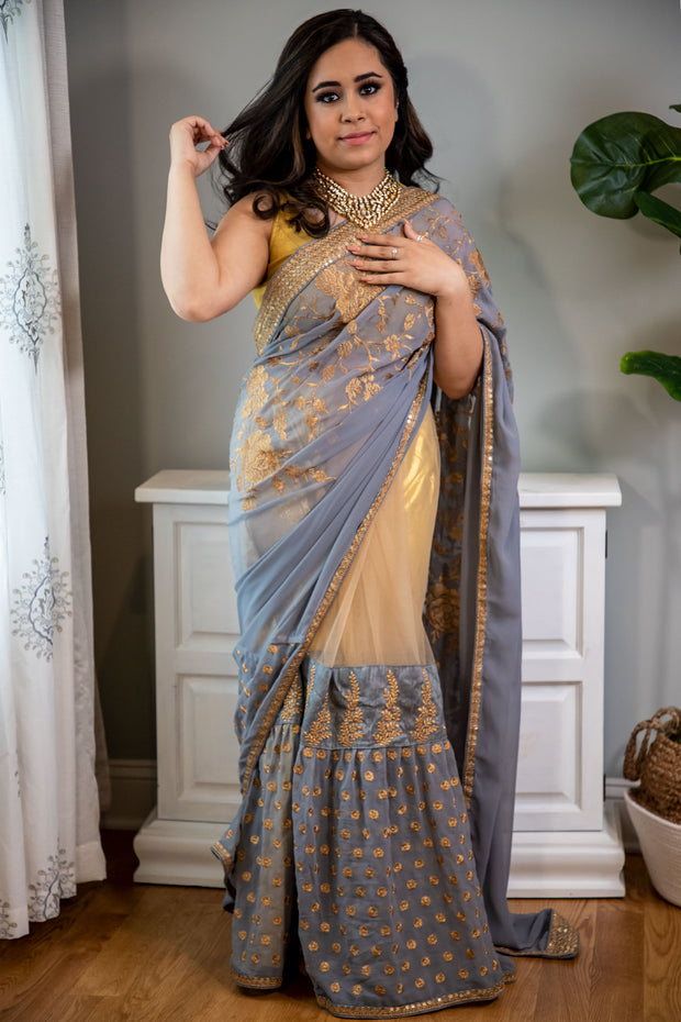 Not your average sari.  A sari that is gray and gold with a unique flare. Beige net overlay paired with wide grey border made to look like a lehnga-sari covered in gold embroidery.