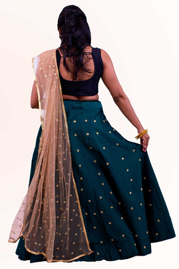 Dramatic two piece lehenga with rich green skirt covered in gold embroidered polka dots. Paired with black blouse. Finish this look with color blocking net gold dupatta with matching polka dots as skirt on shoulders/ shoulder.