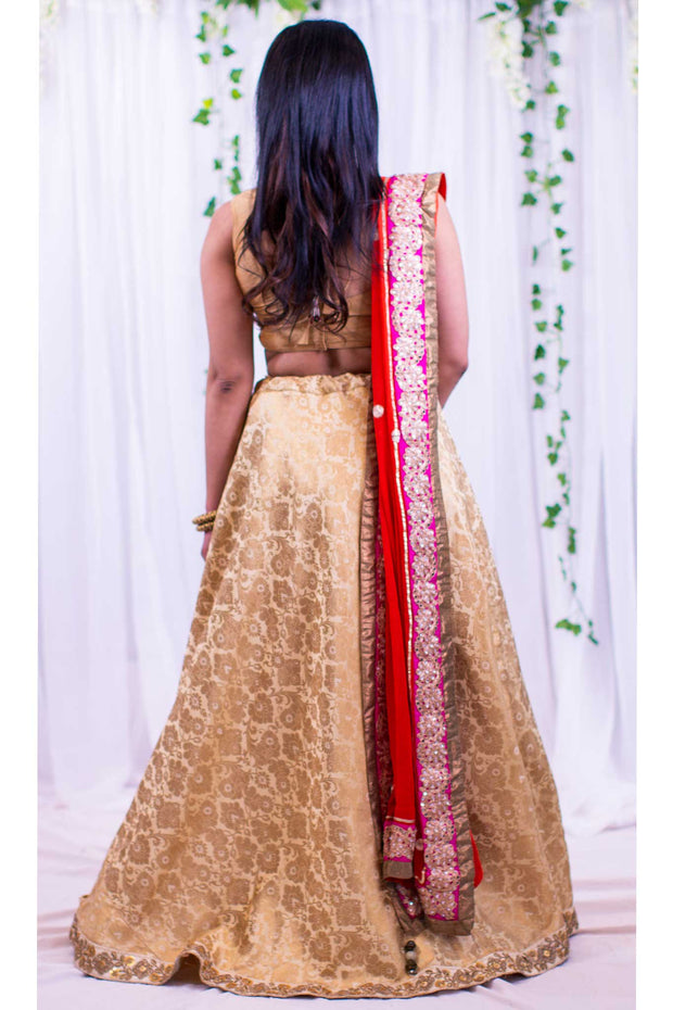 Elegant gold two piece lehenga, using textured flower brocade fabric. Paired with bright orange dupatta full flower design on the border for exuberant draping.