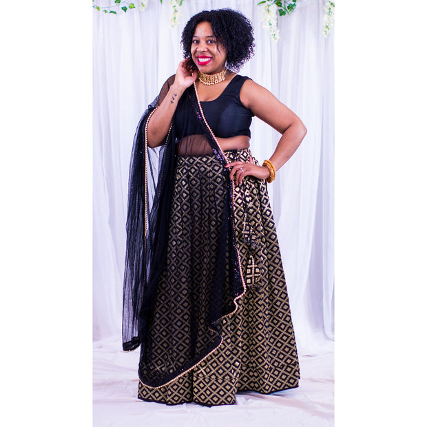 Chic two piece black lehenga, skirt covered in gold embroidered square design. Paired with black chiffon blouse. Finish this look by draping black dupatta with dainty gold trim on shoulders/shoulder.