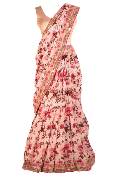 Gorgeous pink floral chiffon sari with embroidered border with pink trim and printed flowers through out the saree. Paired with beige blouse.