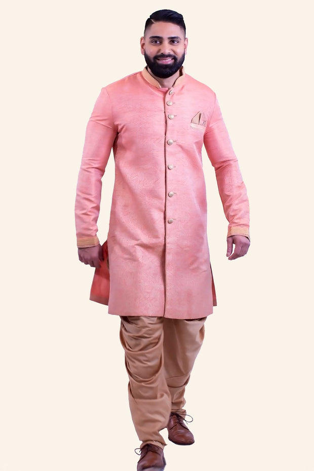 Peach colored royal sherwani with gold buttons, gold pipping throughout the sherwani and detailed gold border at the wrist. Sherwani is paired with dhoti style pants.