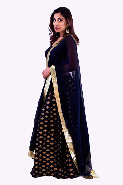 Beautiful two piece silk lehenga, paired with cropped black blouse. Skirt is covered in golden embroidered square pattern. Finish this look by draping black chiffon dupatta with bright gold border on shoulders/ shoulder.