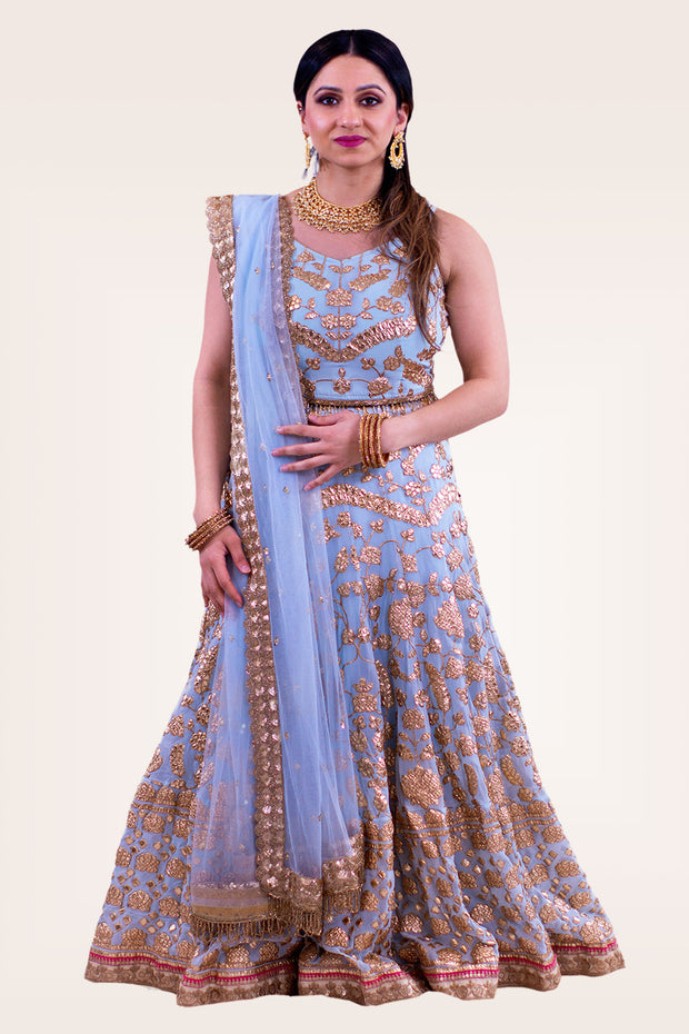 Iridescent light blue blouse with modern strap. Skirt with full of gold flower embroidery crafted from top to bottom with built in can can. Net dupatta with heavy border making it perfect for draping