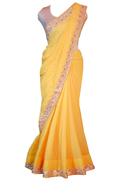 Gorgeous yellow chiffon sari covered in gold specks with champagne color hand work through out the border of the saree. This type of traditional craftsmanship is called gotta patti.