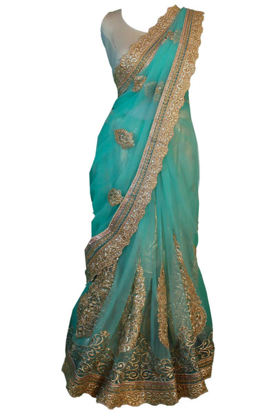 Magnetic light blue/ teal net sari with traditional hand crafted golden embroidery. Heavy pallu detail.