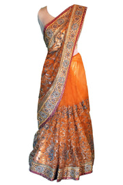 Rustic red blood orange net sari, covered in blue flowers and gold embroidery with extremely heavy detailed pallu.
