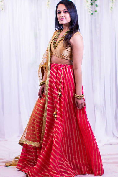 Lavish two piece lehenga with pink skirt, covered in gold stripes. Paired with gold blouse. Finish this look by draping matching net golden dupatta on shoulders/shoulder.