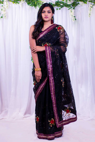 Black berry net sari with pink sequenced border, with embroidered red roses & green leaves.