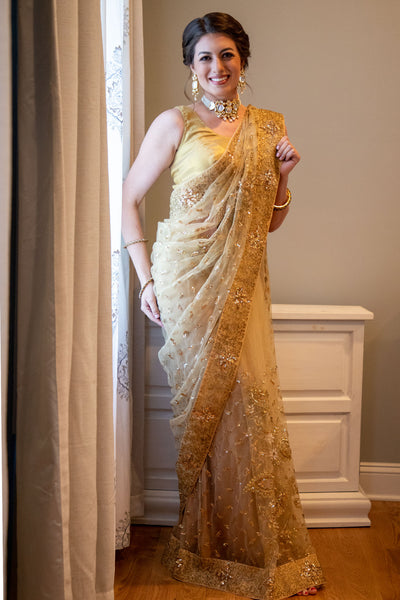 Pink sari covered in gold embroidery with blue border filled with gold flowers.