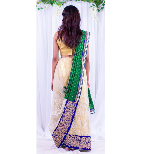Coy white net sari with intricate pattern at the bottom of skirt, with heavy dark blue border. Green pallu with full white flowers.