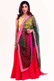 Fashionable two piece lehenga with crimson skirt decorated with dainty gold trim. Paired with gold blouse. Finish this look by draping a net green dupatta on shoulders/ shoulder.