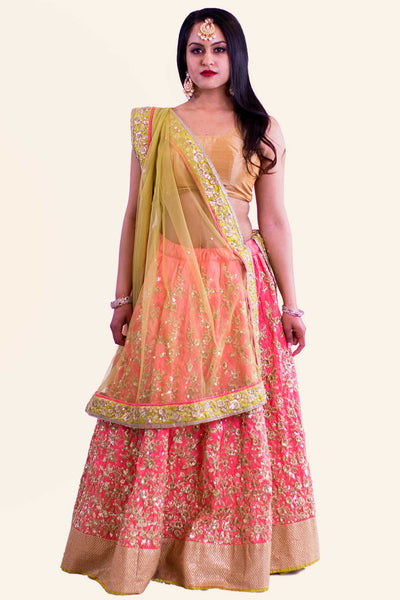 Peachy pink lehenga with complex gold threading designed through entire skirt paired with golden blouse. Finish this look with draping the net color blocking dupatta on shoulders/ shoulder.