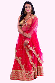 Royal red two piece lehenga with heavy golden embroidered border on skirt, paired with modest beige blouse. Finish this look with red net dupatta with flared golden border on shoulders/ shoulder.