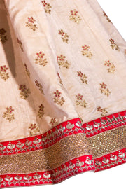 Royal two piece bridal lehnga, with cream skirt designed with small intricate gold flowers, thick sparkly golden border with red trim for contrast. Paired with red blouse covered in gold embroidery with small peacock feather pattern. Finish this bridal look by draping red net dupatta with gold border on shoulders/ shoulder.
