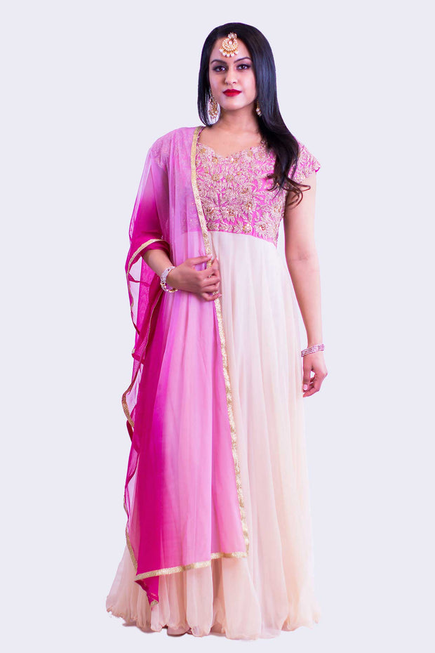 Gorgeous gown with hot pink top covered in gold embroidery and sequence with designer neckline and flared sleeves. Flowy and romantic almond colored bottom.
