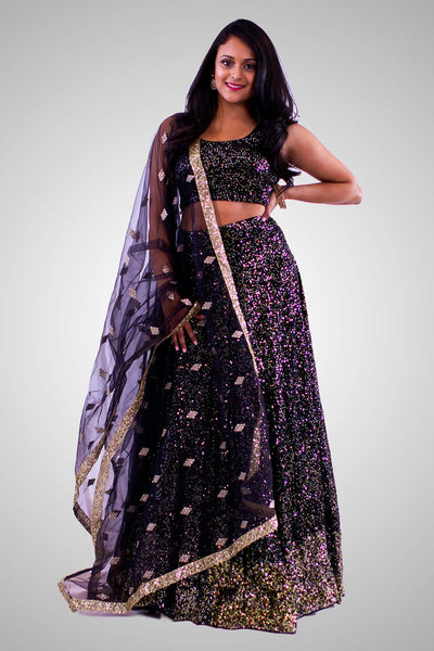 Stylish black lehenga completely covered in gold sequins on skirt and blouse. Finish this look by draping black net dupatta on shoulders/ shoulder.