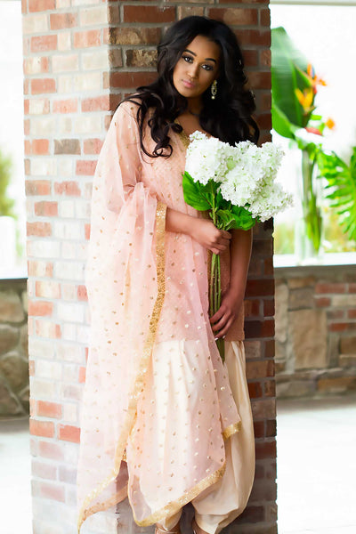 Elegant pink kurta covered in scalloped gold work, paired with matching ruffled pants designed with a draw string to fit any size waist. Finish this look with matching pink glittery dupatta by draping it on shoulder.