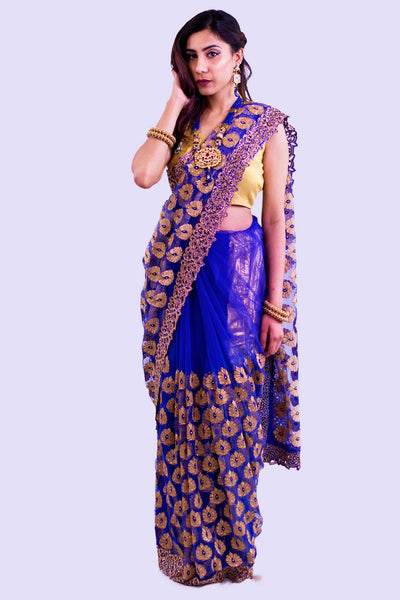 Royal blue net sari covered in iridescent gold embroidery. Pallu is decked in golden trim for high sophistication.
