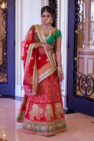 Traditional bridal lengha, red skirt covered in gold embroidered elephants for good luck, color contrasting green border. Paired with green blouse hand crafted gold work. Finish this traditional look with an extremely festive red net dupatta with hints of green on the golden border.