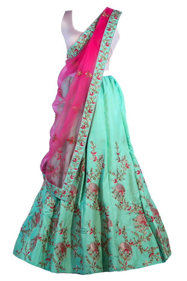 Divine light green lehenga with complex embroidery of red, pink and gold flowers on skirt. Finish this look by draping hot pink dupatta with light green border on shoulders/ shoulder.