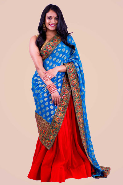 Phenomenal color blocking two piece lehenga, bright red skirt paired with golden blouse. Blue dupatta is focal point of this look, designed with heavy red and orange embroidered border.