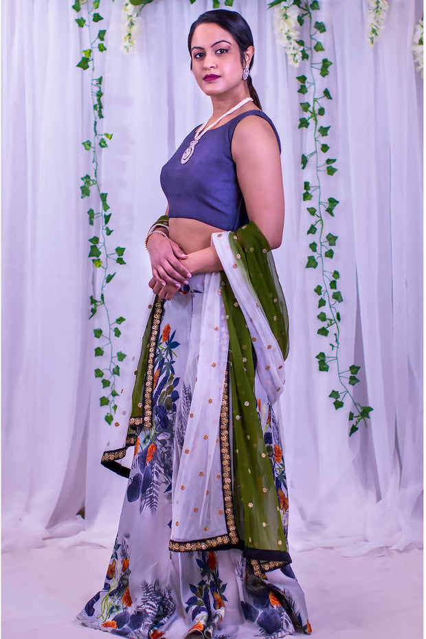 Modern blue blouse, paired with dark toned floral skirt. Finished with a two toned dupatta with gold border.