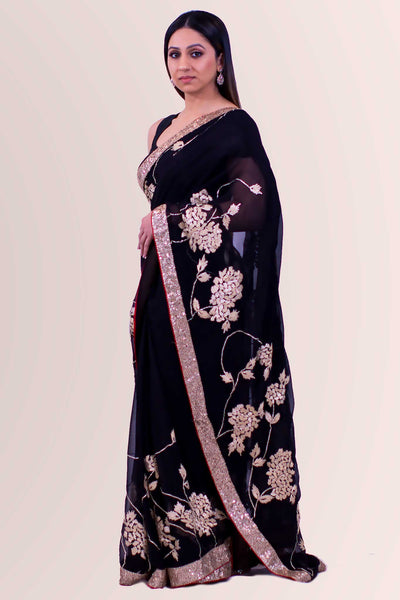 Majestic black chiffon sari with heavy gold border with dainty red trim.