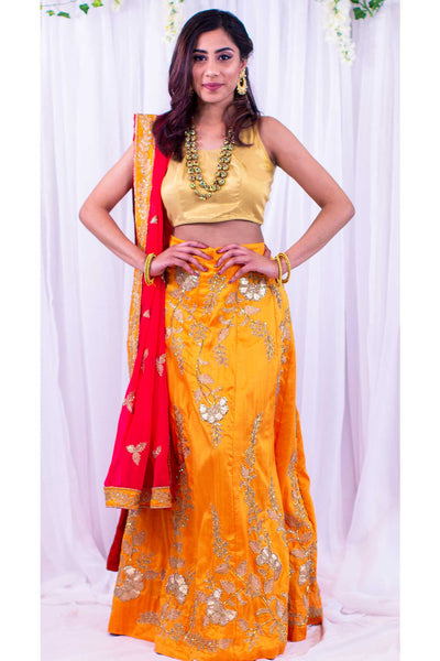 Beautiful two piece yellow-orange lehenga, skirt embellished with silver hand crafted embroidery. Paired with gold blouse. Finish this look with draping color blocking yellow and pink dupatta with silver work on the border.